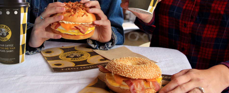 Couple eating Einstein Bros. bagel egg sandwiches with coffee