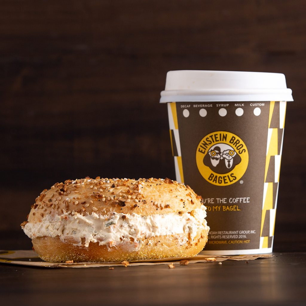 image of a cup of hot Einstein Bros. coffee next to a bagel with shmear.